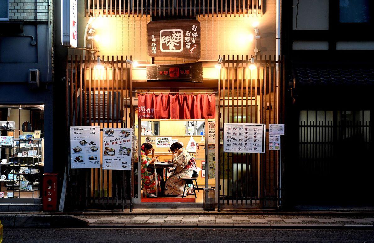 Dois turistas aguardam sua refeição vestindo trajes tradicionais. O aluguel de quimono no inverno e de ...