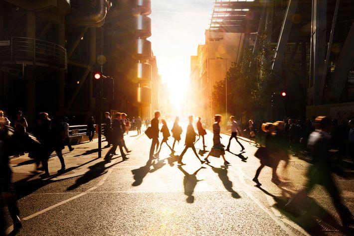 Pedestres caminham pelas ruas de uma cidade inglesa ao amanhecer.