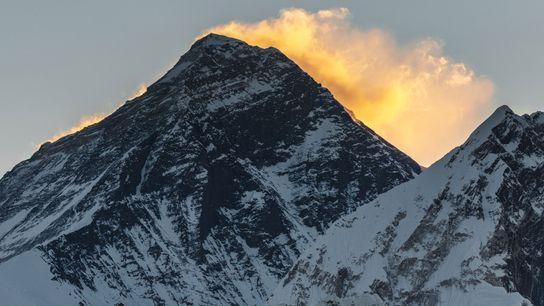 Os primeiros raios do sol da manhã brilham sobre o pico do Monte Everest.