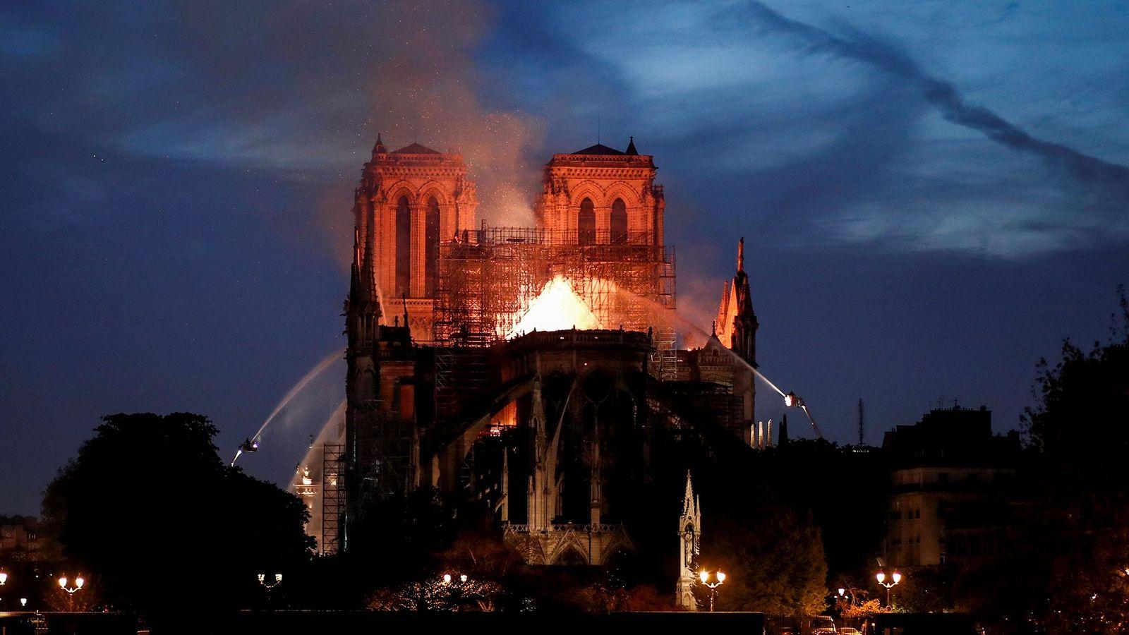 Os bombeiros apagam as chamas da Catedral de Notre Dame em chamas em Paris, na França, ...
