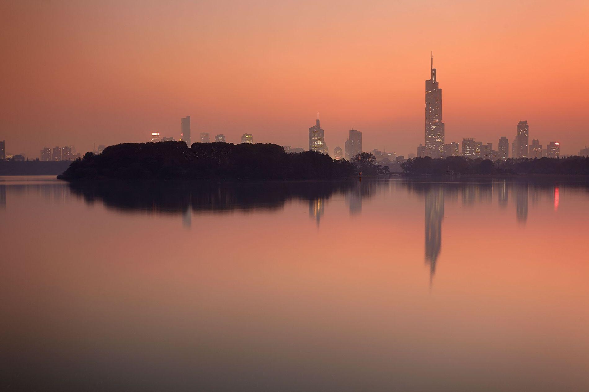 O pôr do sol emoldura o horizonte da cidade de Nanquim, à beira do lago Ziwu, ...