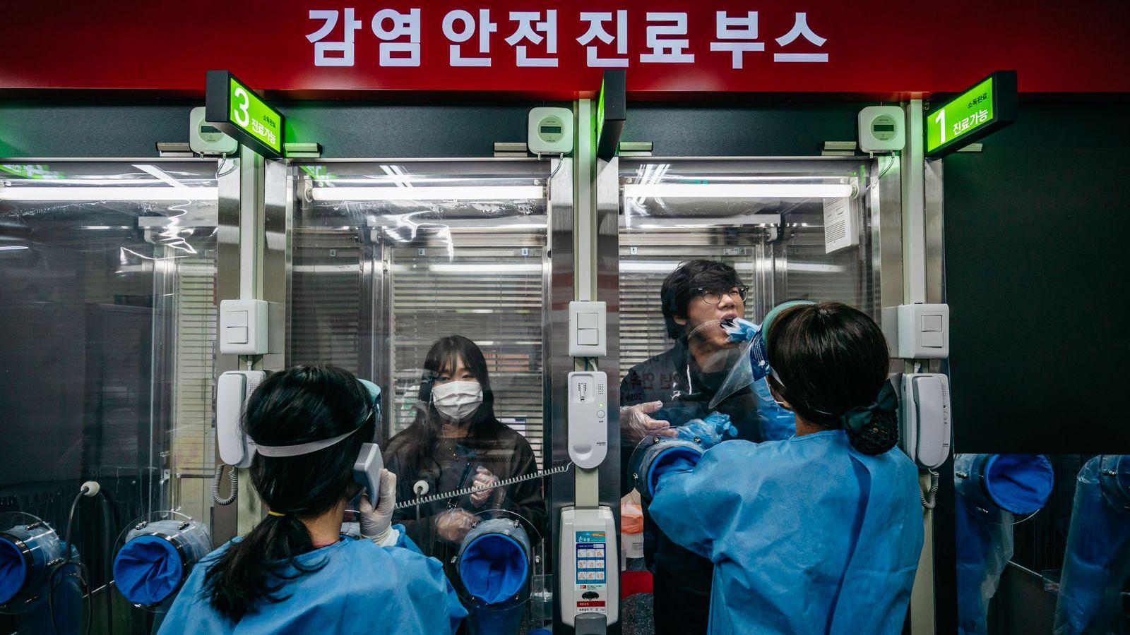 Profissionais da saúde coletam amostras do nariz e da boca em uma clínica-ambulatório no Hospital H ...