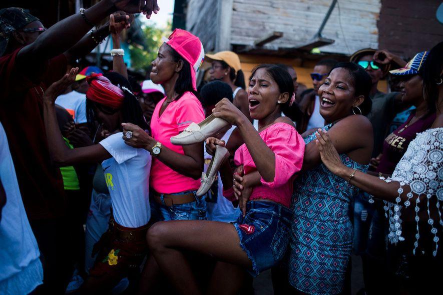 Grupo de pessoas dança e celebra um feriado em uma rua lotada na ilha.
