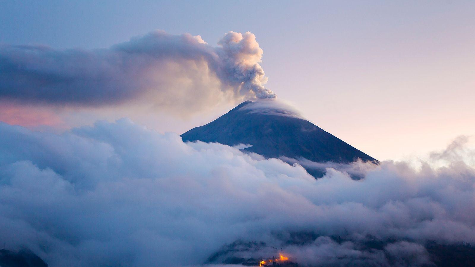 Vulcão Tungurahua em erupção durante o crepúsculo. As erupções vulcânicas representam uma forma pela qual a ...
