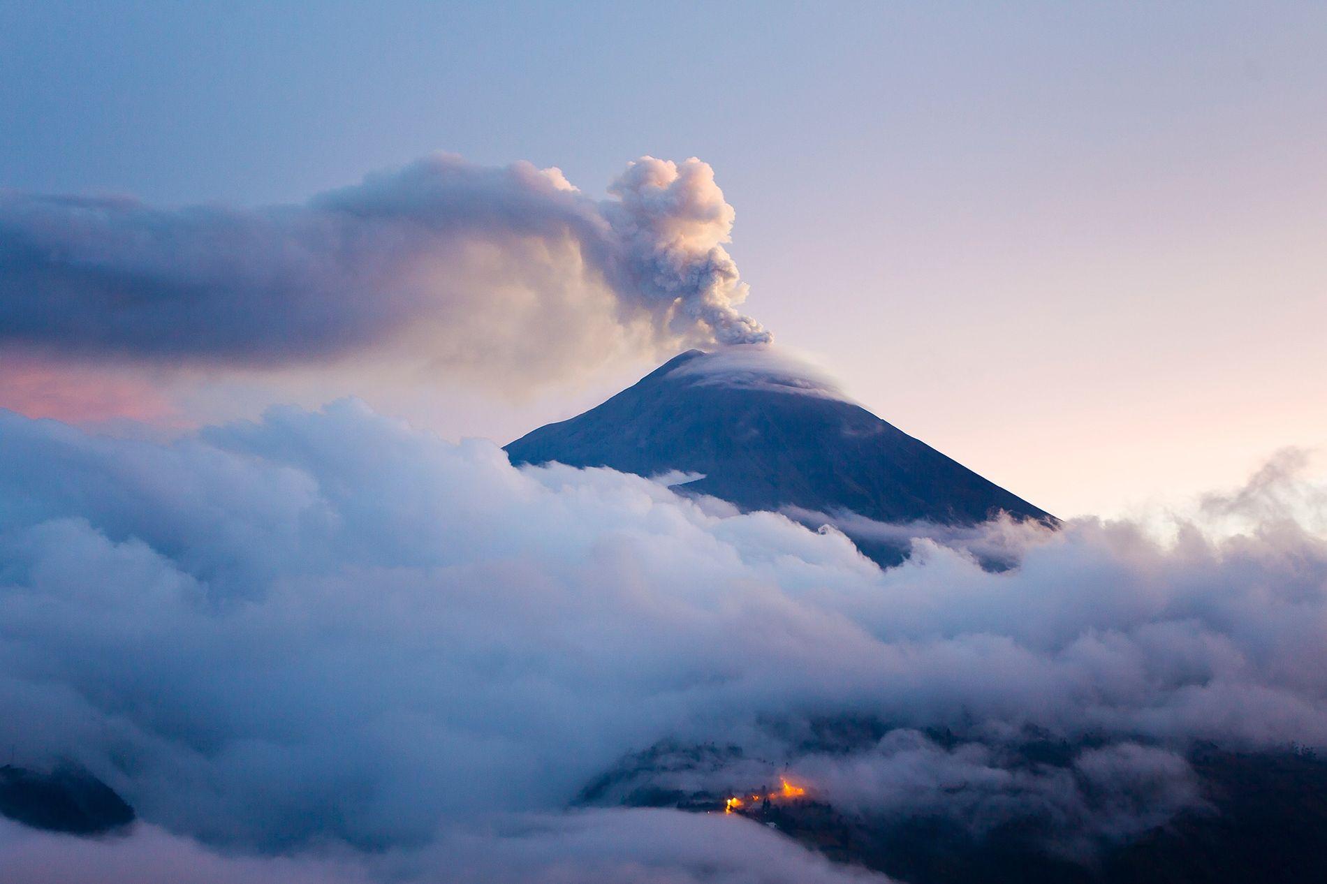 Vulcão Tungurahua em erupção durante o crepúsculo. As erupções vulcânicas representam uma forma pela qual a Terra devolve seu carbono interno à superfície.