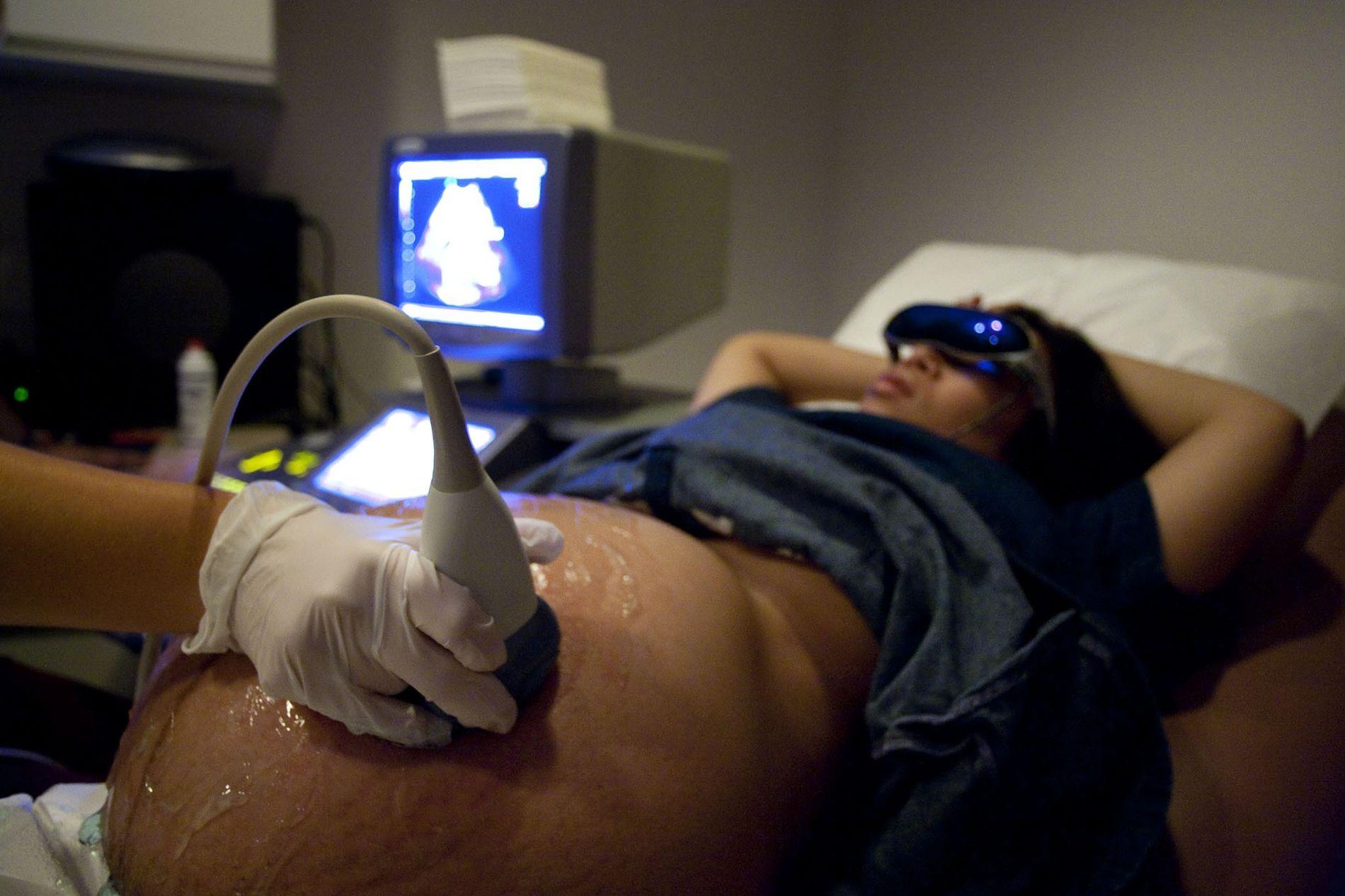 Uma mulher grávida recebe uma ultrassonografia de inspeção para seus bebês gêmeos.