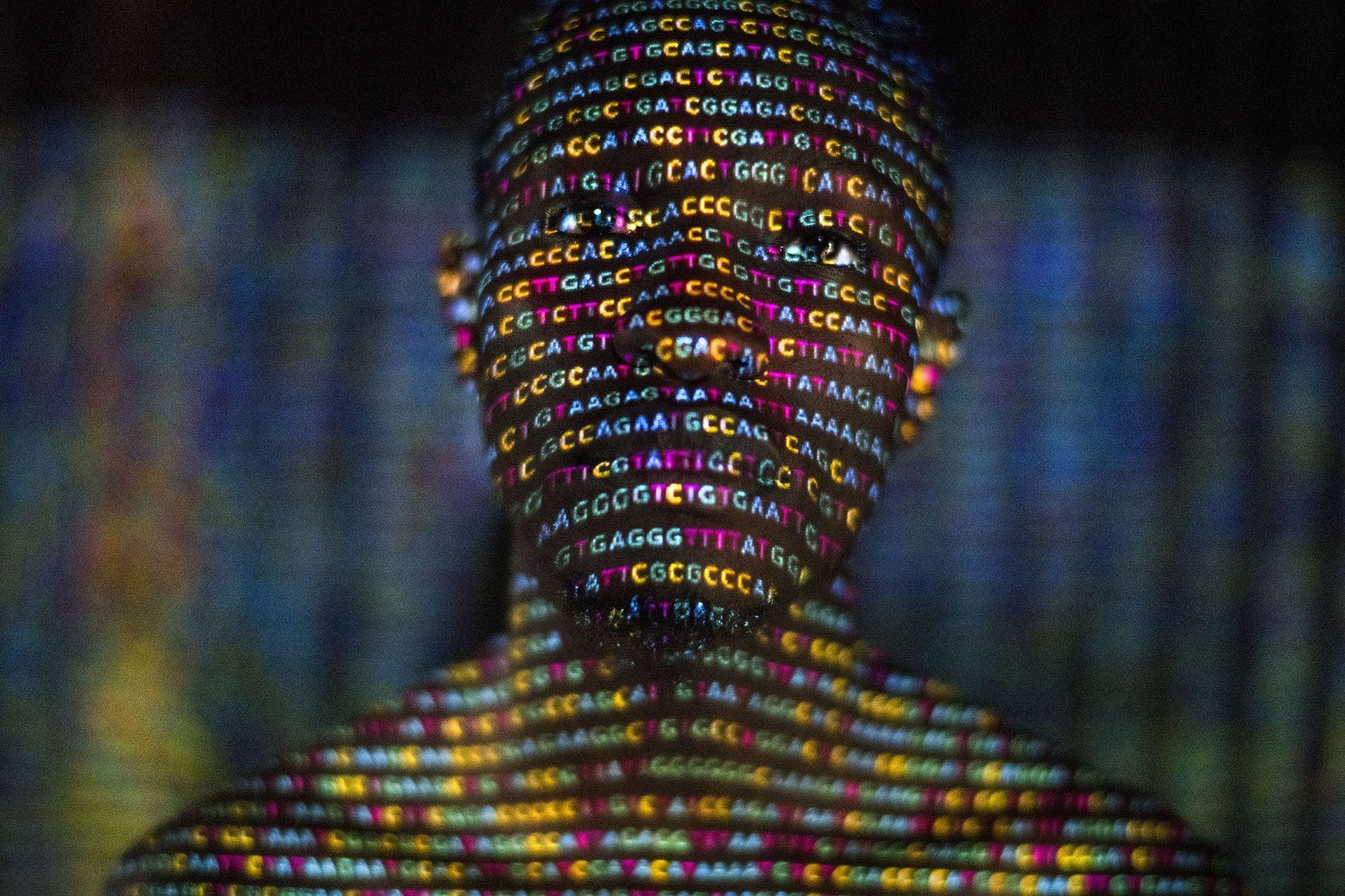 As quatro letras do código genético - A, C, G e T - são projetadas em um homem ugandense.