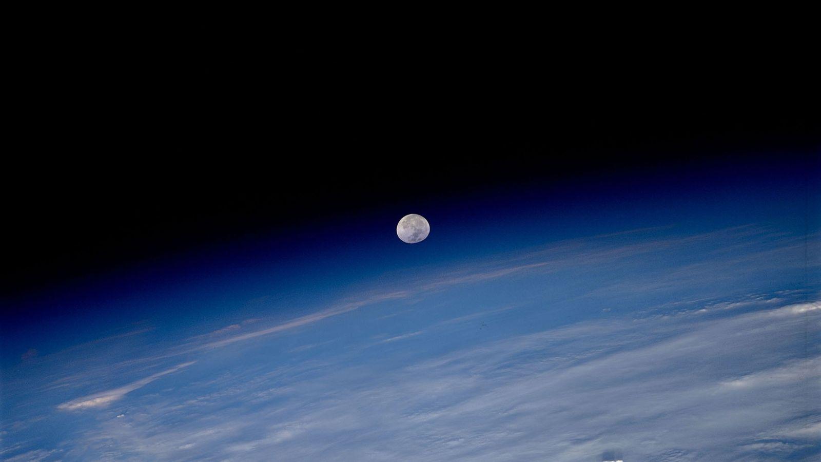A lua parece estar pendurada no limite entre a atmosfera da Terra e a escuridão do ...