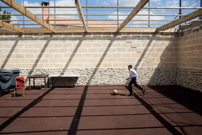 Jovem judeu brinca no pátio da Grande Sinagoga de Sarcelles, subúrbio da classe operária de Paris. ...