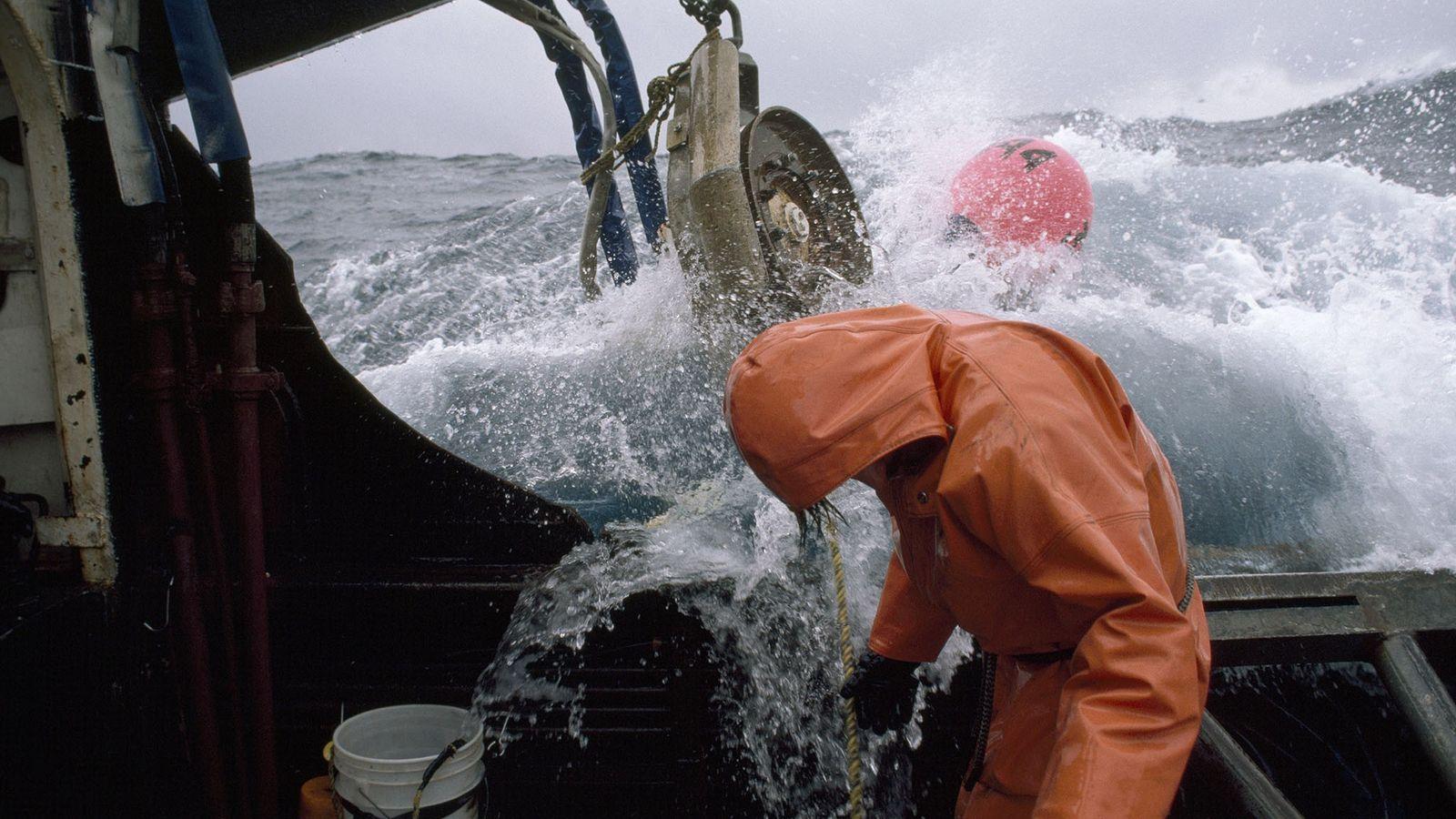 Um pescador checa as linhas de pesca em alto-mar. O alto-mar são as águas fora da ...