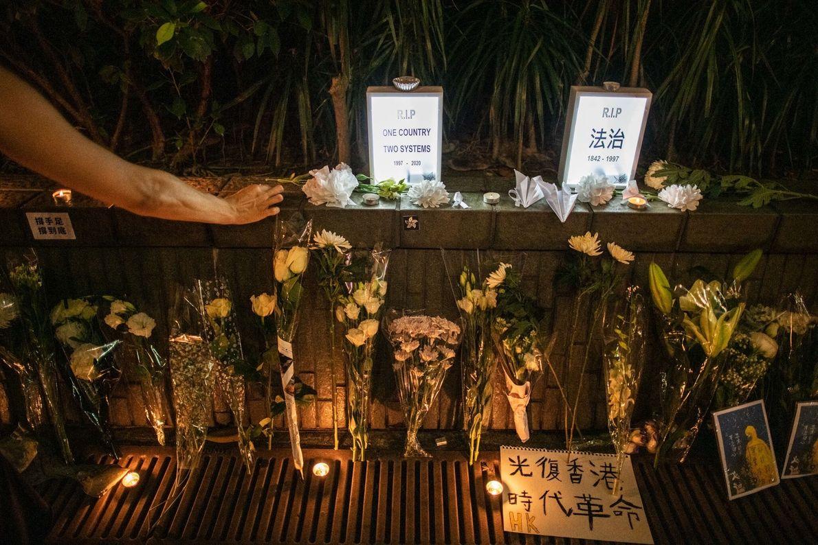Em julho, uma mulher em Hong Kong presta sua homenagem em um memorial improvisado para Marcus ...