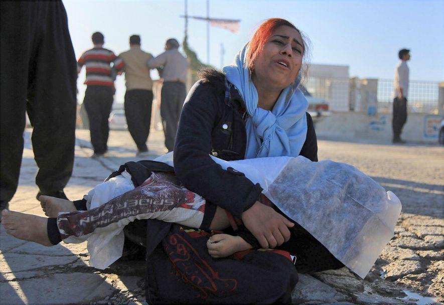 Mulher chora ao segurar o corpo de sua filha, morta no terremoto, em Sarpol-e Zahab, no …