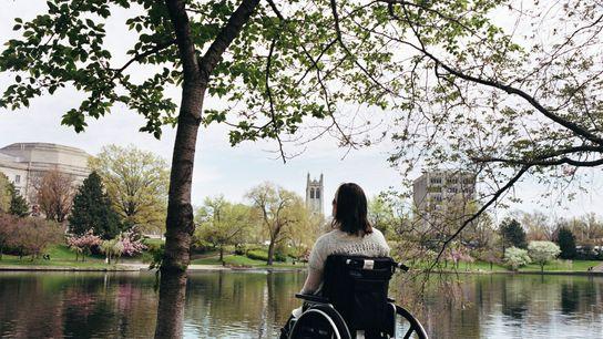 Katie senta embaixo de uma árvore perto da Lagoa Wade em Cleveland, Ohio. Em uma caminhada ...