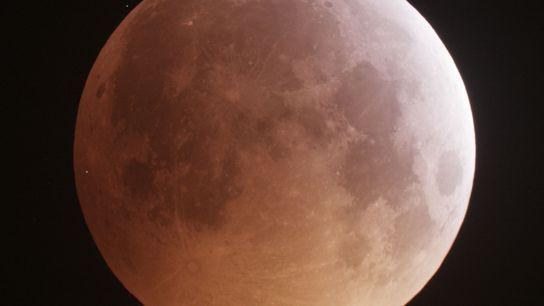 Um ponto branco brilhante no canto esquerdo da Lua indica o impacto de um meteoro durante ...