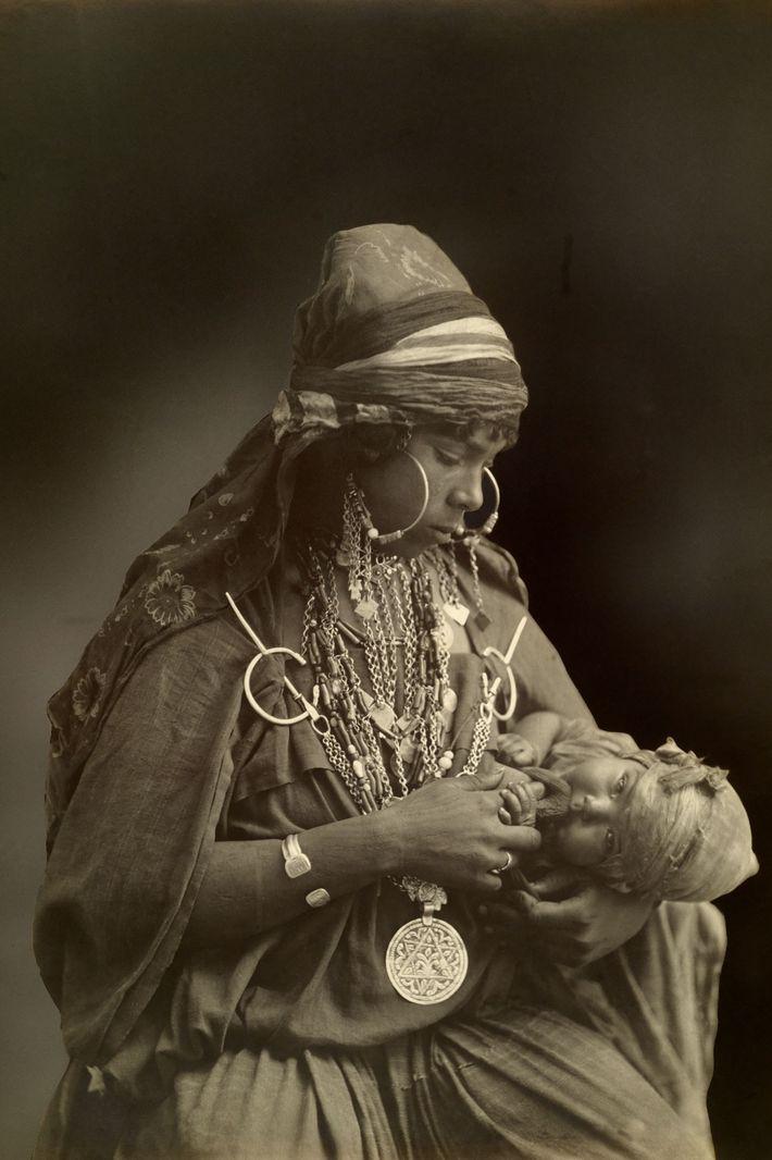 Uma mãe beduína, elaboradamente enfeitada com joias, olha para seu filho no início dos anos 1900.