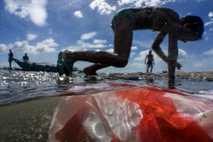 Crianças brincam na costa da baía de Manila, poluída por lixo doméstico, plástico e outros tipos ...
