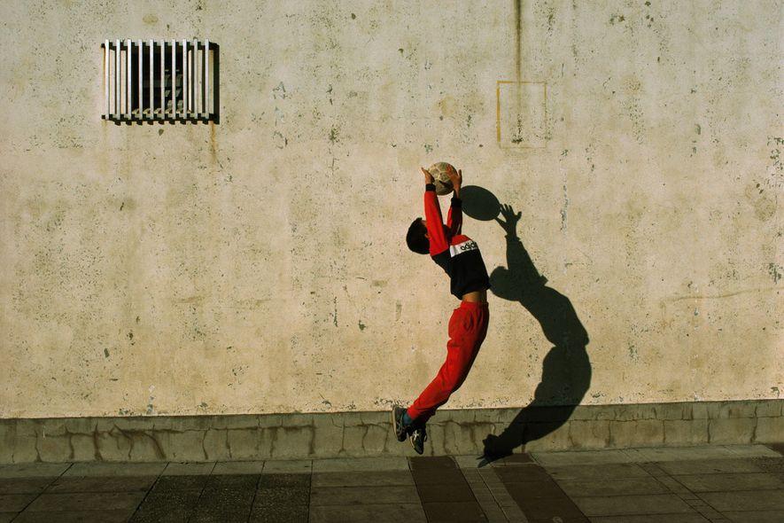 Durante um jogo de futebol em uma escola em Tóquio, Japão, um goleiro salta e estende ...