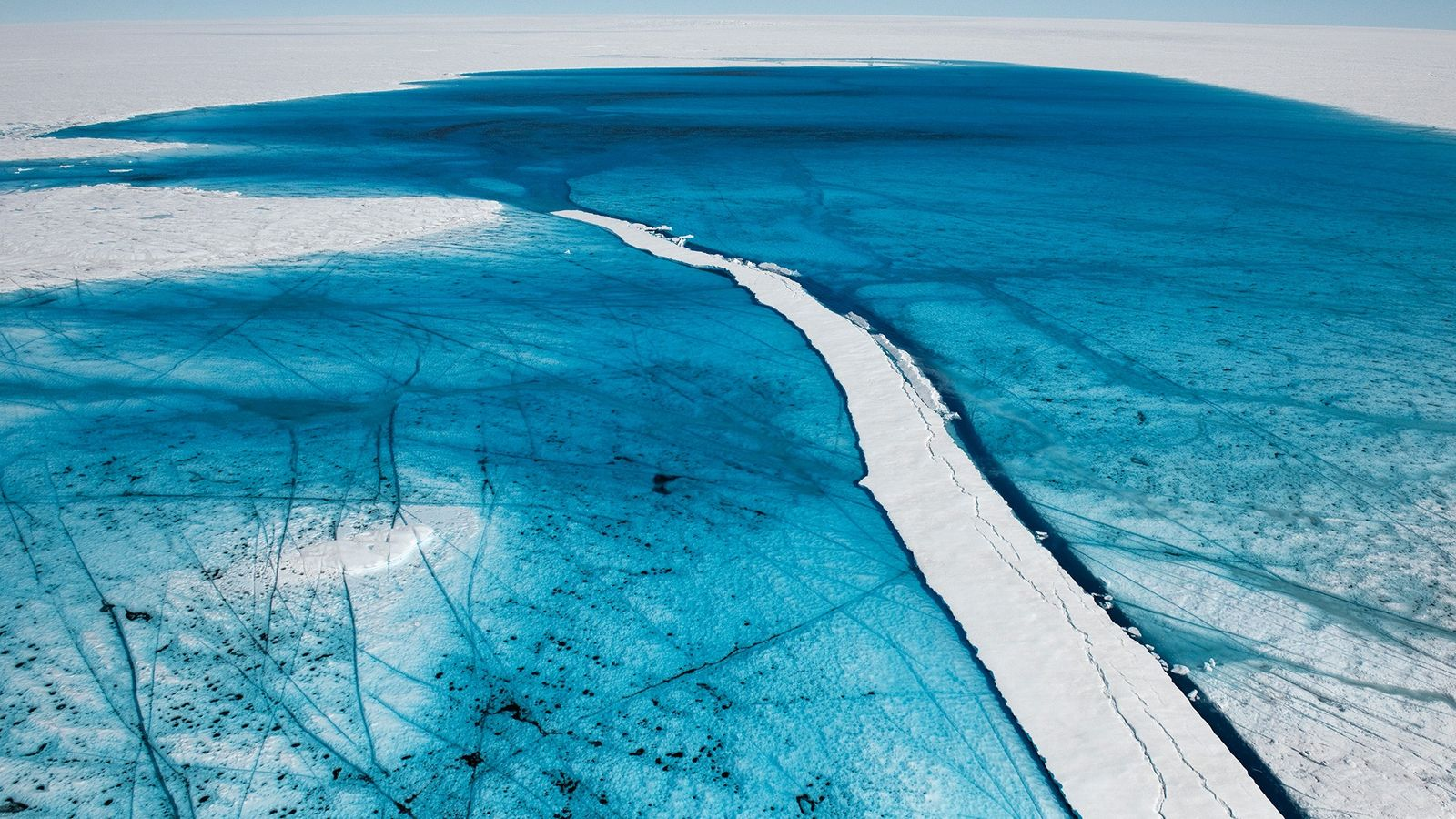 Águas derretidas durante o verão se acumulam em um lago na superfície da camada de gelo ...