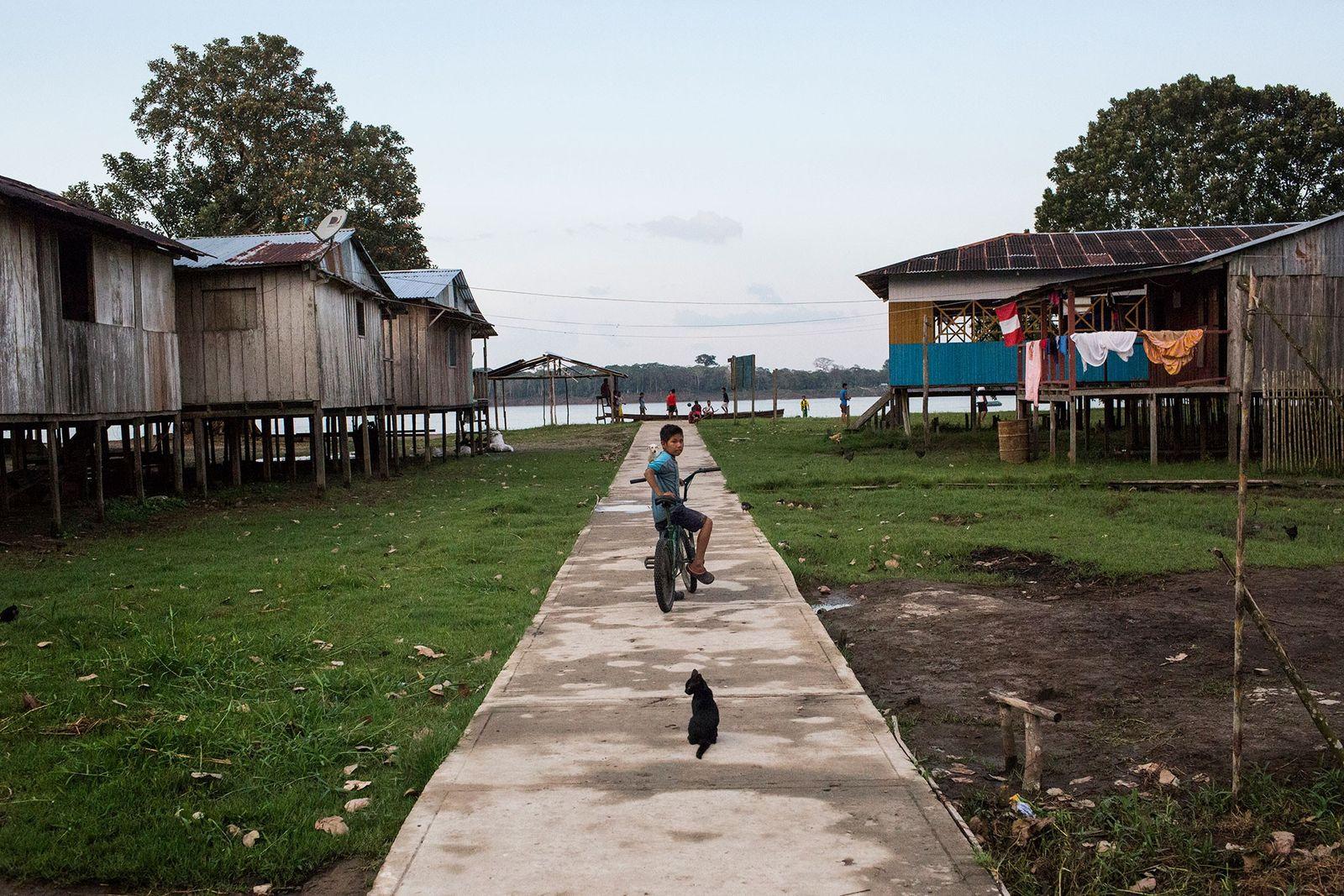 Um menino e um gato param em um caminho em Puerto Alegría, uma pequena comunidade peruana ...