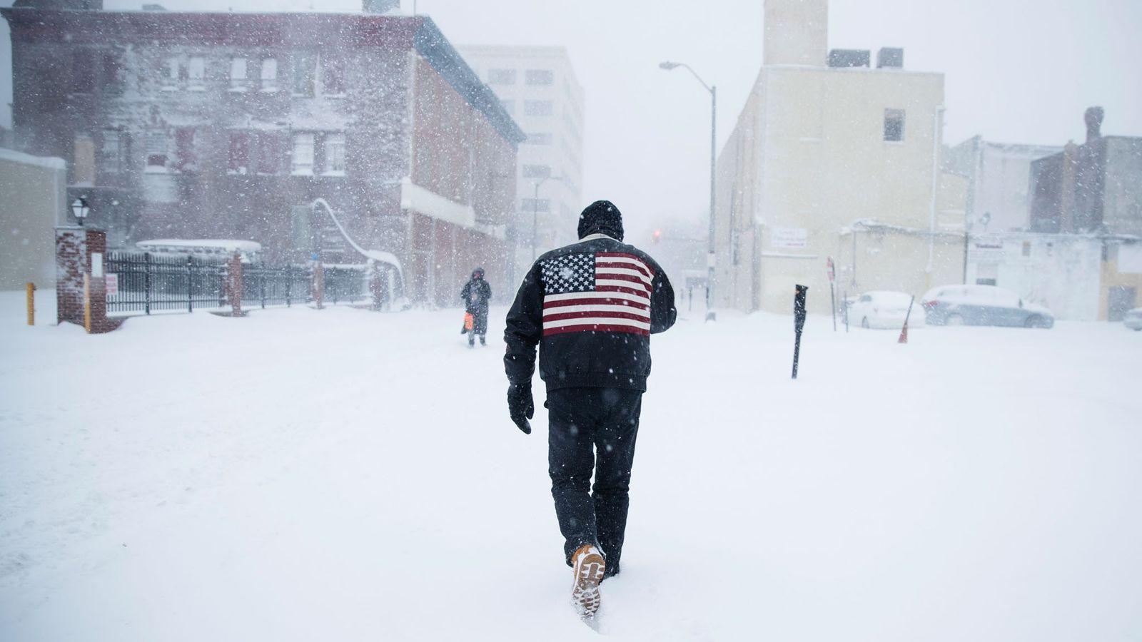 Um homem abre caminho em meio a uma tempestade de neve ocorrida no inverno, em Atlantic ...
