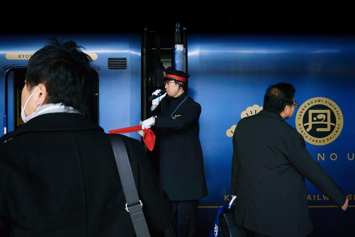 Um funcionário vestindo luvas brancas na estação anuncia a saída de um trem. Os funcionários utilizam ...