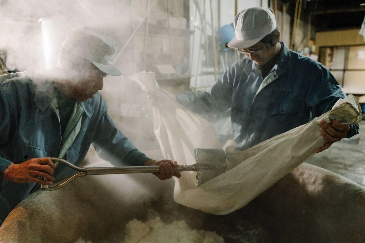 Dois trabalhadores, ou kurabito, de uma fábrica de saquê, começam a vaporizar o arroz do saquê ...