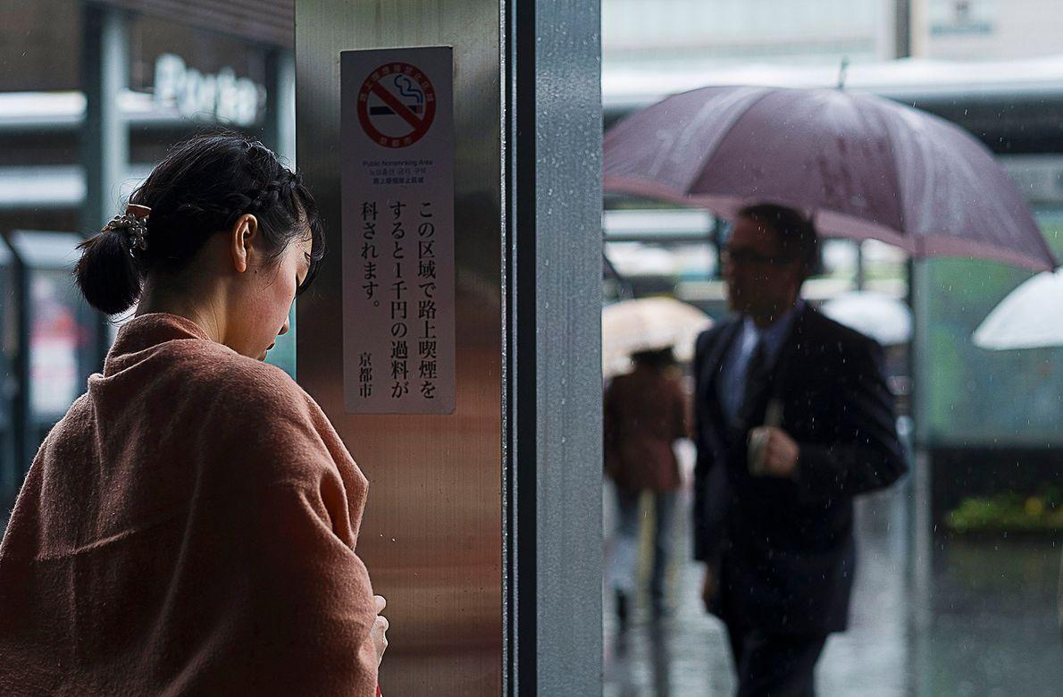Uma passageira se esconde da chuva em uma estação de trem local. Assim como Tóquio, a ...