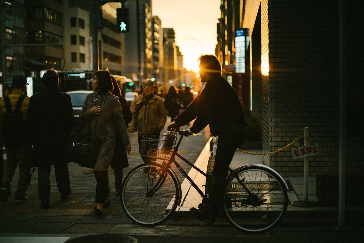 O pôr do sol lança um tom dourado sobre uma rua de trânsito intenso em Quioto.