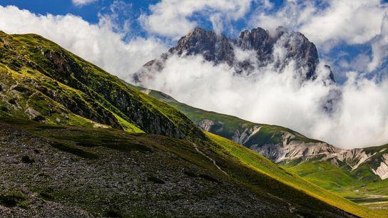 O Corno Grande, o pico mais alto da cordilheira dos Apeninos, destaca-se dentre as nuvens. Os ...