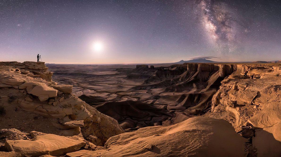 A silhueta de um fotógrafo solitário em Moab, Utah, em contraste com o céu escuro que ...