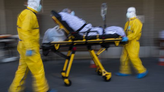Devido à superlotação, um paciente com coronavírus é transferido de hospital por membros da equipe médica ...