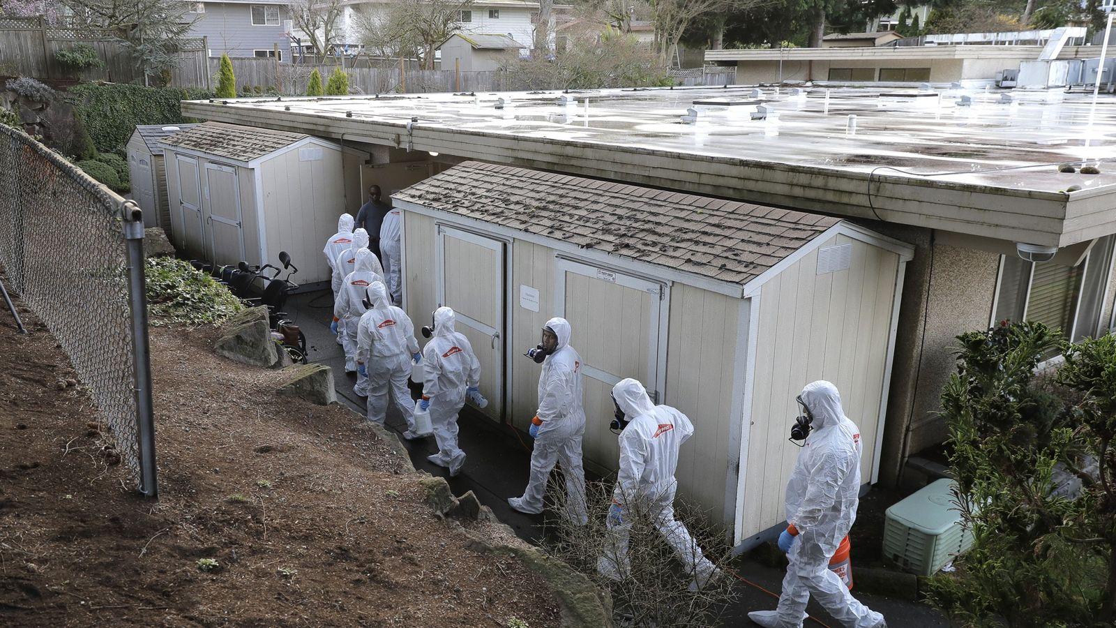 Trabalhadores de uma equipe de recuperação de desastres da Servpro usando trajes de proteção e respiradores ...