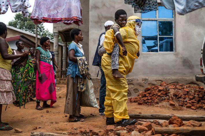 Um trabalhador de saúde carrega Kakule Kavendivwa, 14 anos, para uma ambulância em Beni no ano ...