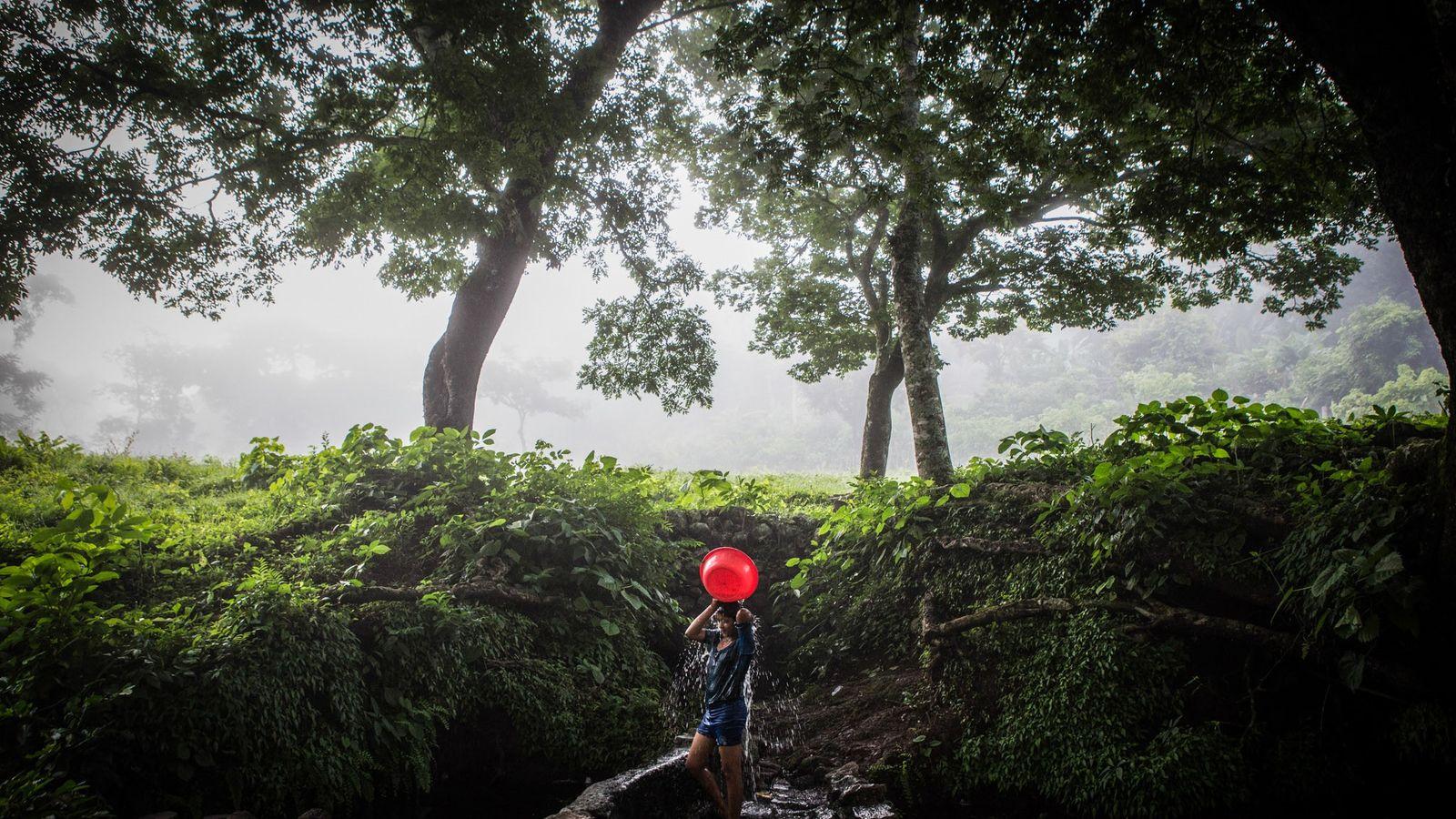 Uma menina lava o cabelo em um poço ao amanhecer em uma pequena comunidade em Cabañas, ...
