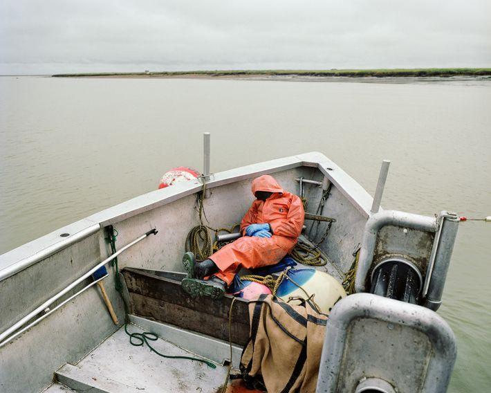 Um pescador exausto tira um cochilo num barco pesqueiro na Baía de Bristol, no Alaska.