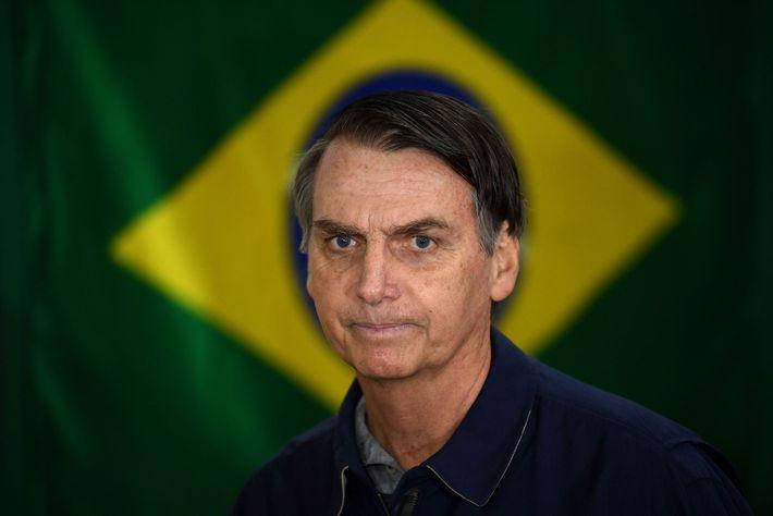 Bolsonaro, líder do Partido Social Liberal (PSL), de direita, posa diante da bandeira brasileira no dia ...