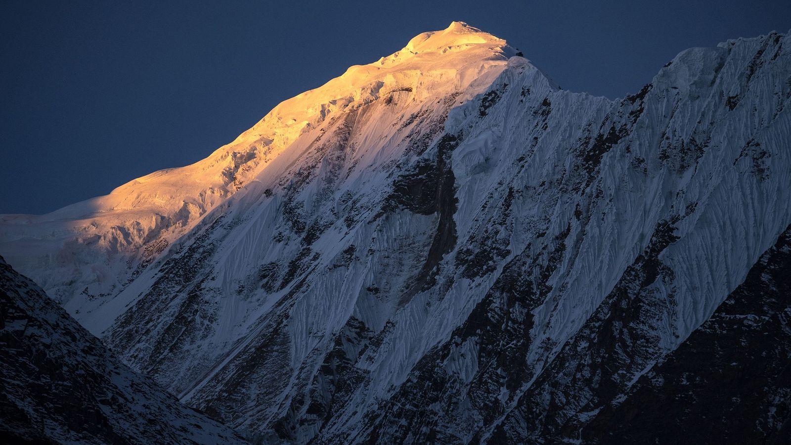 O sol atinge os picos do Himalaia em 8 de novembro de 2018, visto de Manang, ...