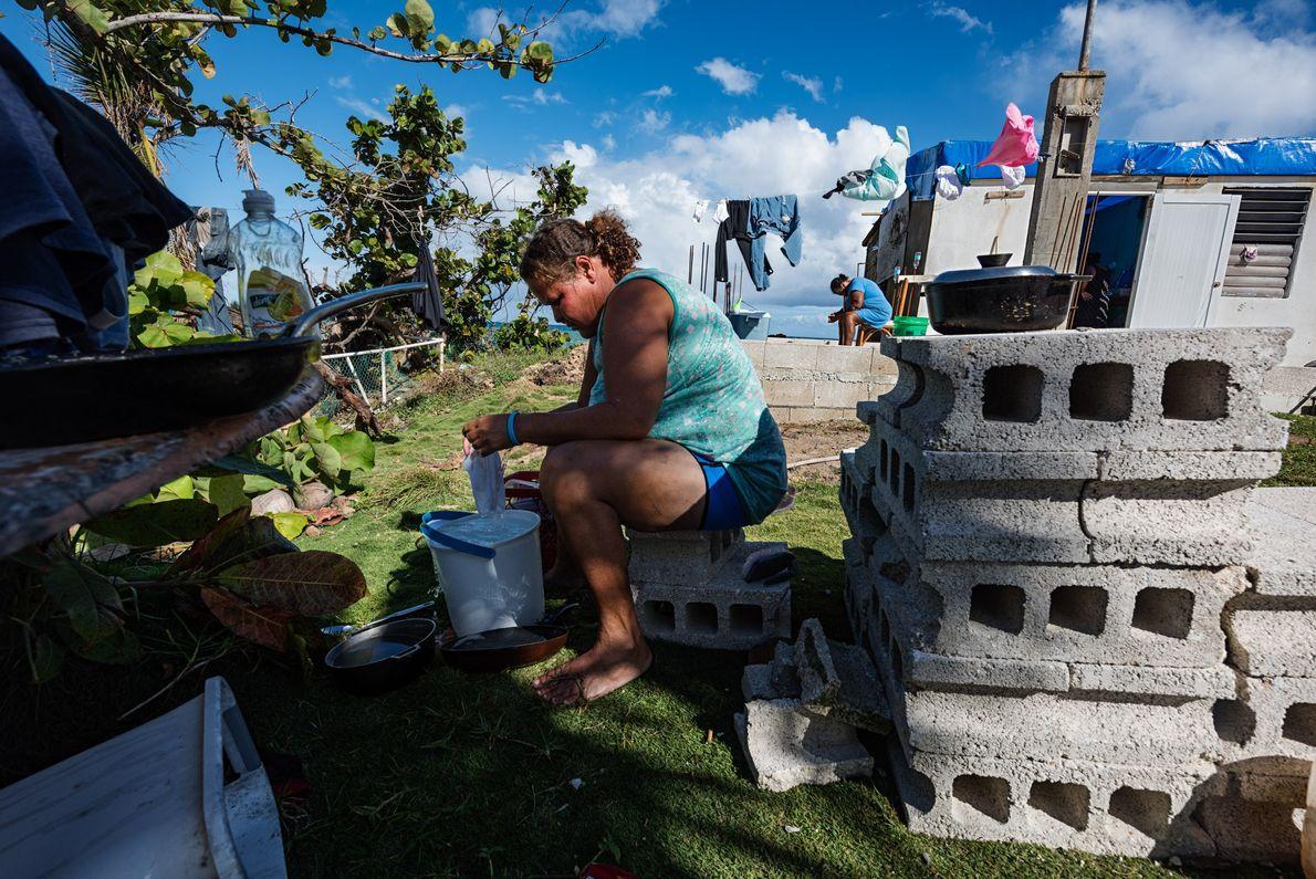 Yasmin Morales Torres, 41, lava a roupa a mão em seu quintal em Playa El Negro, ...
