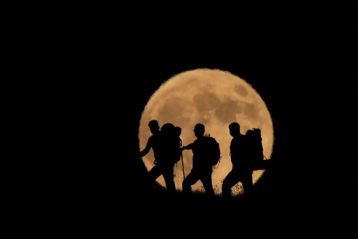 A Lua cheia aparece no horizonte atrás da silhueta de escaladores do monte Artos, na Turquia, ...