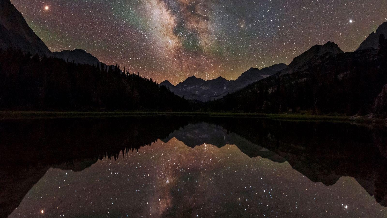 A Via Láctea em uma abóbada celeste sobre um lago nas montanhas da Califórnia. A partir ...