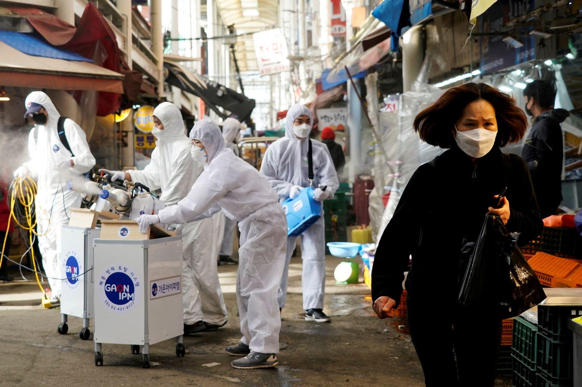 Mulher com máscara para evitar contrair o coronavírus se afasta enquanto funcionários de uma empresa de ...