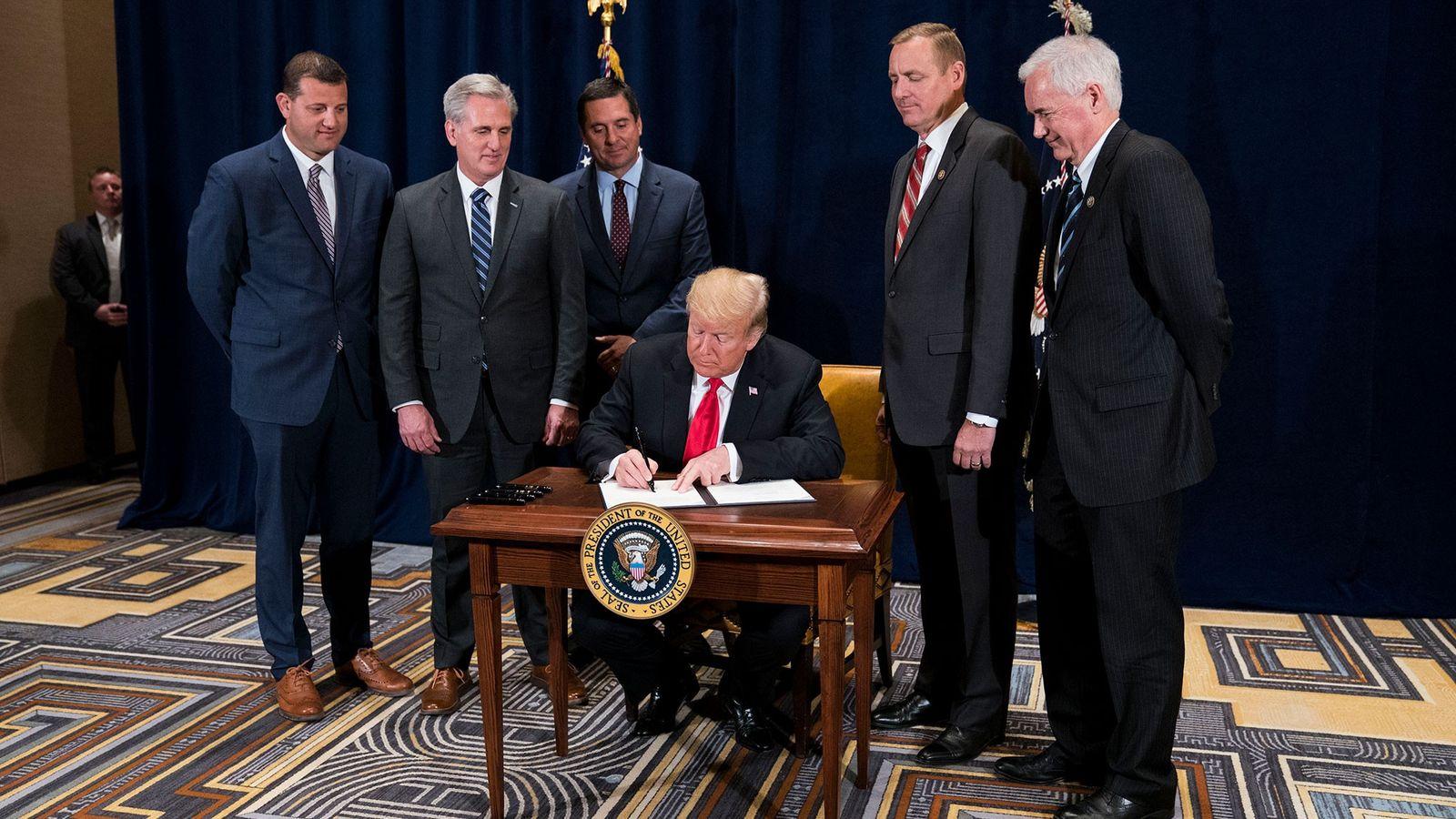 """O presidente Donald Trump assina um memorando presidencial para """"minimizar ônus regulatórios desnecessários"""" em 19 de ..."""