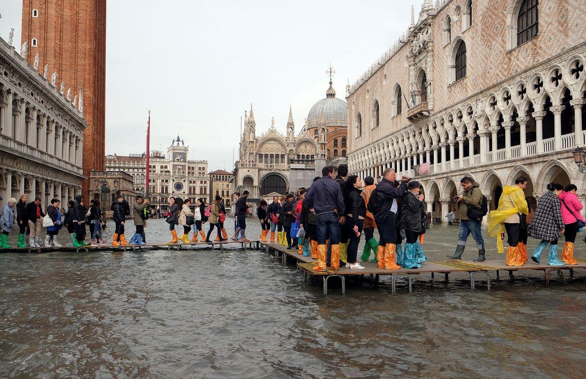 Pessoas caminham por uma passarela na Praça de São Marcos, inundada durante um período sazonal de ...