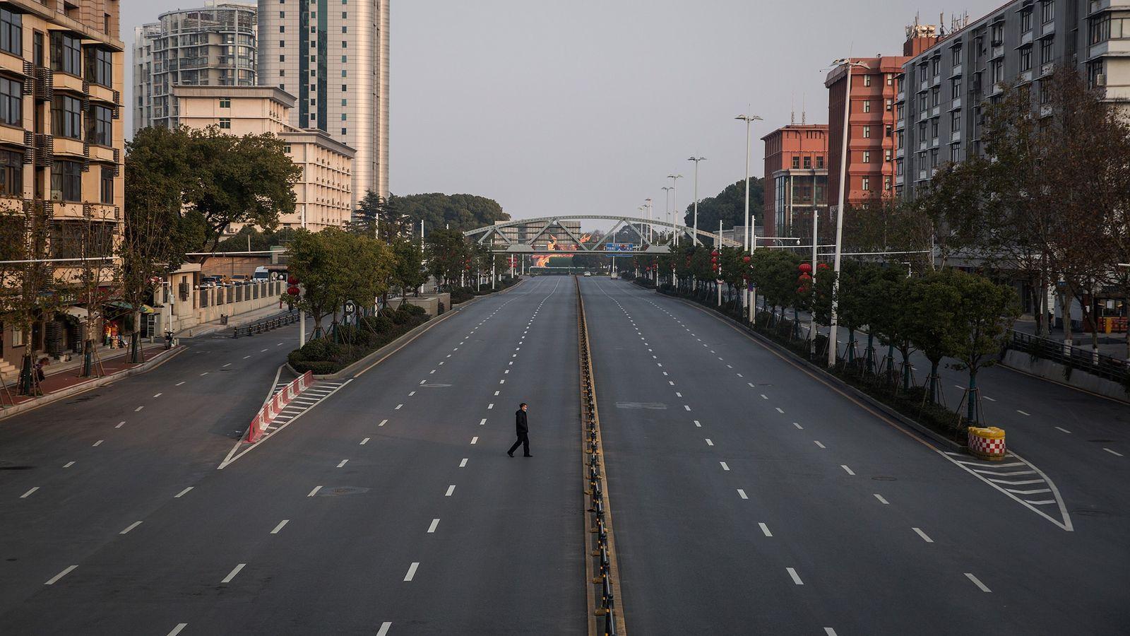 Um homem atravessa uma avenida vazia em 3 de fevereiro de 2020 em Wuhan, na China. ...