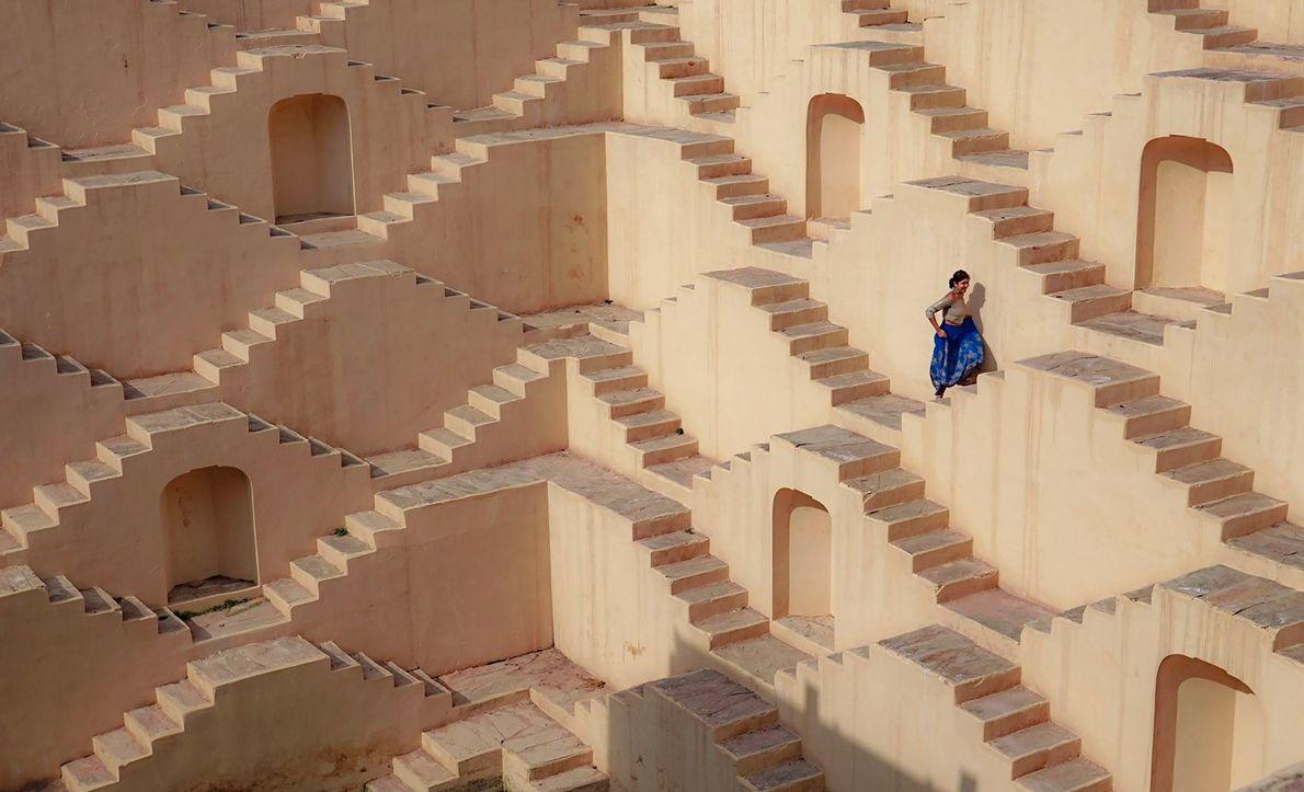 JAIPUR, ÍNDIA  A vestimenta azul vibrante de uma mulher se destaca entre as escadarias ao estilo …