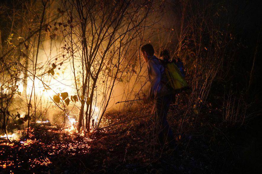 Jovens voluntários de Roboré, cidade a cerca de 30 quilômetros de Aguas Calientes, tentam extinguir as ...