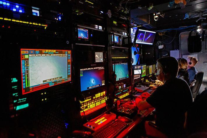 Dentro da sala de controle, os tripulantes pilotam veículos operados remotamente (ROVs) e observam as telas ...
