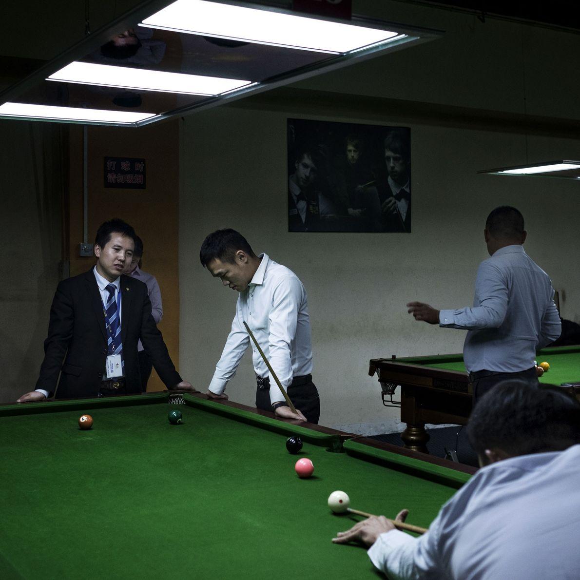 Um grupo de agentes imobiliários que vive em bunkers subterrâneos joga bilhar em um estabelecimento local.
