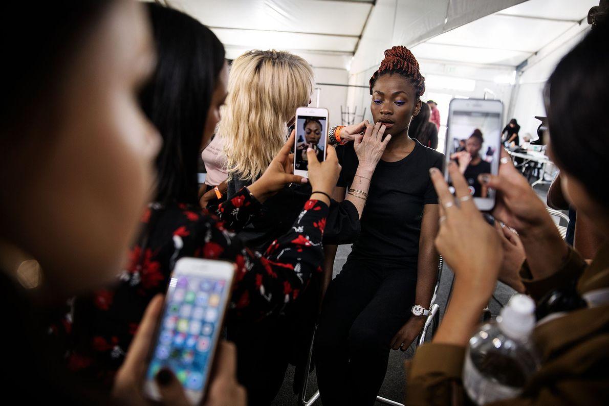 Modelo sul-africana negra é maquiada por maquiadora branca em evento de moda de Johanesburgo.