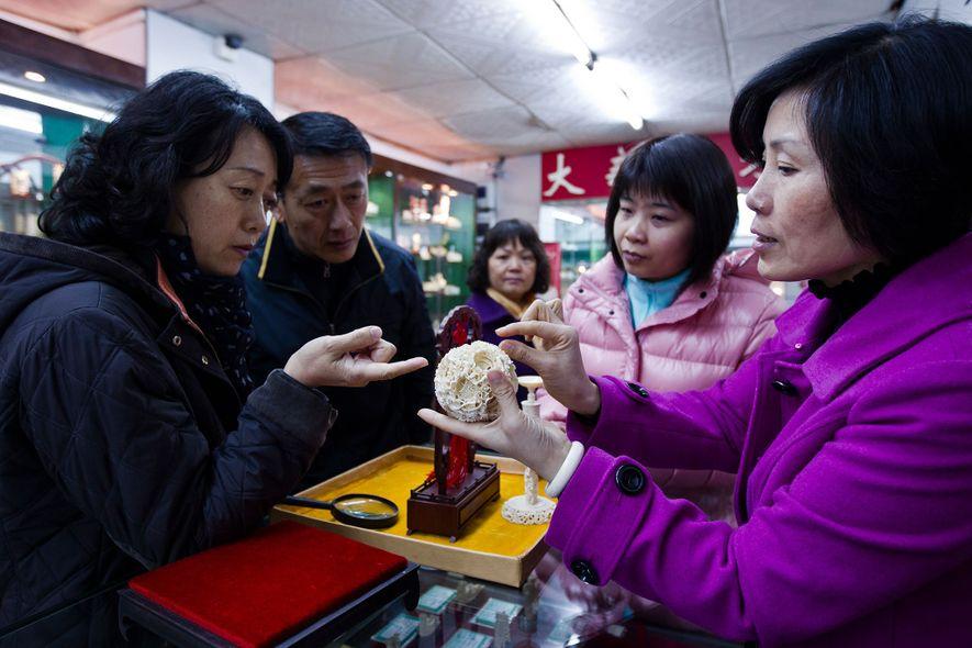 Compradores admiram um ornamento de marfim em um estabelecimento de propriedade estatal em Guangzhou, China, em ...